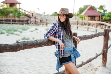 Smiling woman cowgirl standing and leaning on fence