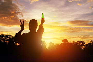 Recess Fitting Buddha Silhouette woman raised hands holding a green beer bottle on the sunset sky,