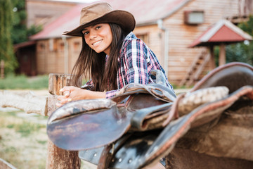 Smiling brunette young woman cowgirl leaning on fence in village