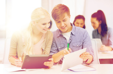two smiling students with tablet pc and notebooks