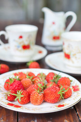 Mature, appetizing strawberries scattered on the white plate.