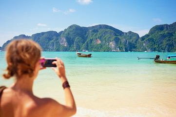 Travel lifestyle. Female tourist taking photo of beautiful lagoon on smartphone.