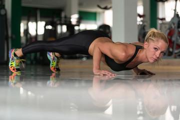 Young Woman Doing Push Ups On Floor
