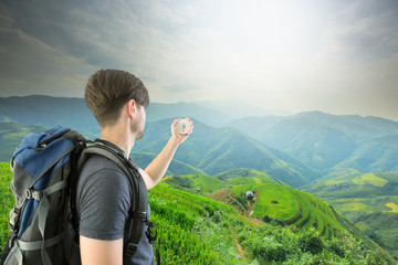 Young Man Traveler holding compass and backpack relaxing outdoor with Rice fields on terraced of Mu Cang Chai,
