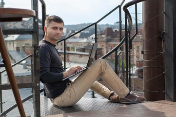 Man portrait with laptop on the background of the city.