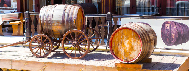 Wine background with old wooden cart and barrel