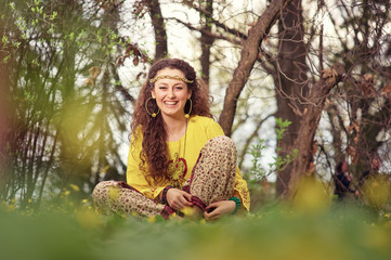 Hippie and youth. Beautiful young woman with curl hair sitting on green grass in park.