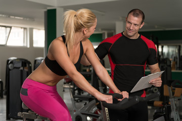 Woman Train Bicycle On Machine With Personal Trainer