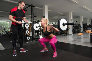 Woman Train Legs Squat With Personal Trainer