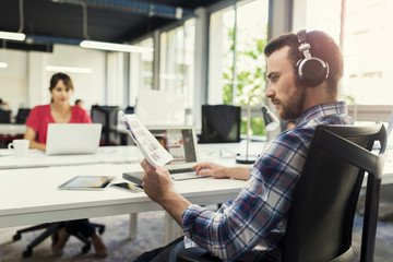 Serious man working on laptop while listening to music in office