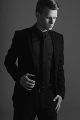 Fashion vogue style studio portrait of young male model posing in black stylish formal suit with tie