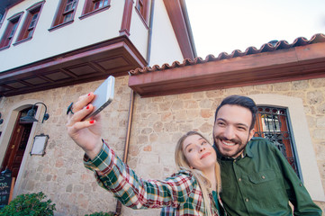 Capturing fun. Beautiful young loving couple bonding to each other and making selfie by their smart phone while walking by old european town.