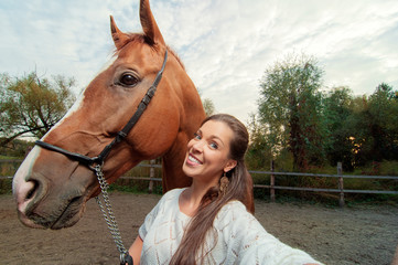 Funny selfie with my friend! Attractive smiling young woman holding camera and making selfie with her horse outdoors