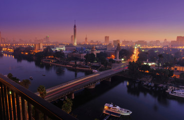 CAIRO - EGYPT - DECEMBER 2010: panorama of Cairo and Nile, movement in morning, sunrise, view from top, with Cairo Tower, buildings, auto and boats.