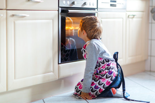 Boy looking at muffins in oven