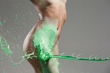 The beautiful woman with green liquid paint over her body
