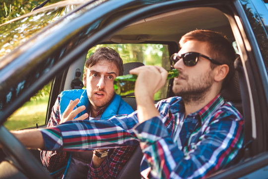dangerous driving - young man drinking beer and driving car, while friend sees danger and looks scared - drinking alcohol in vehicle and road accidents concept
