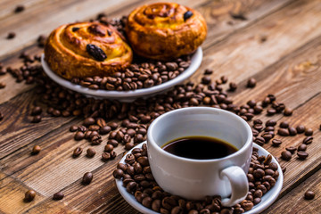 Coffee cup with coffee bean and cinnabons on wooden background.