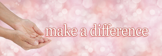 Make a difference charity campaign background - female hands cupped gesturing for donations with the words MAKE A DIFFERENCE floating away on a light pink bokeh background
