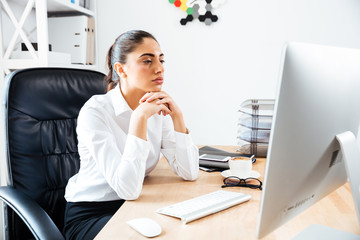 Concentrated smart businesswoman looking at computer screen
