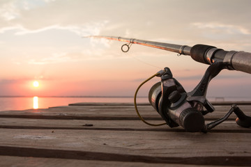 Fishing reel and rod lying on wooden pier over the sunset lake