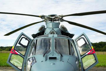 Modern grey helicopter front frontal side. Doors into cockpit of rotorcraft are open