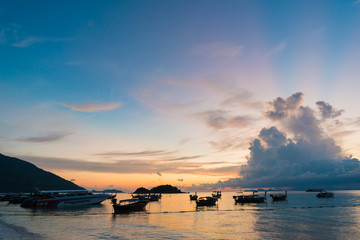 The fishing and travel boat toward the sun light at sunrise at L