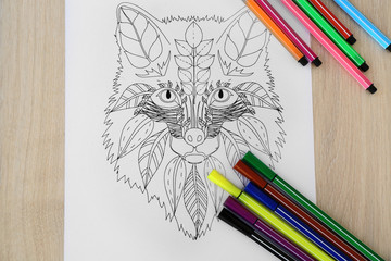 Adult anti stress coloring and soft tip pencils on wooden table, top view