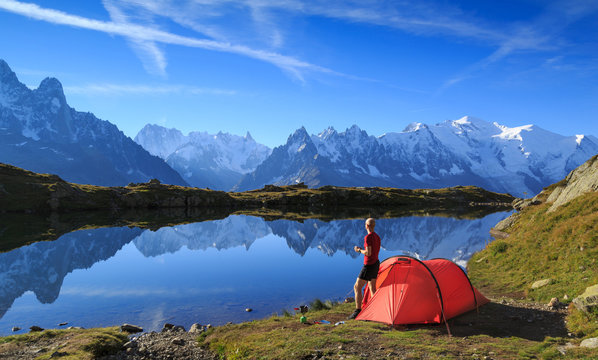 Hiker enjying the view at his red tent in the mountains near Chamonix, France.