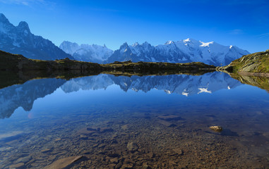 Fotomurales - Mountains and sky reflected in Lac De Cheserys, Chamonix, France.