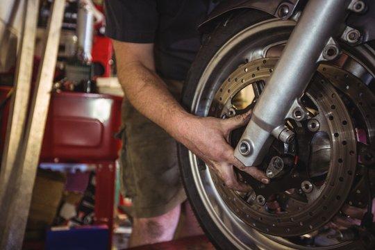 Mechanic examining a motorbike disc brake