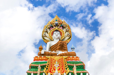 big colorful buddha statue sitting thai temple on blue sky background