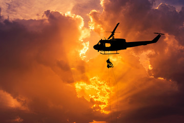 Foto op Canvas Helicopter silhouette soldiers in action rappelling climb down with military mission counter terrorism assault training on sunset background