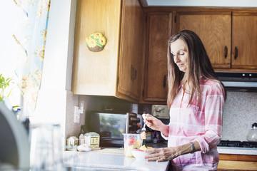 Senior woman standing in a kitchen, preparing food.