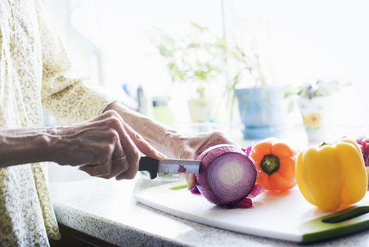 A woman standing in a kitchen, cutting a red onion and peppers on a chopping board.