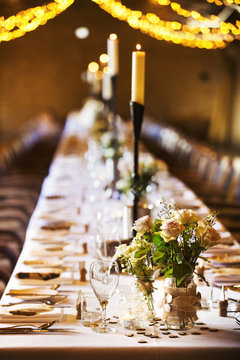 A wedding venue decorated for a party, with fairy lights and a long table set for dinner.