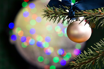 Christmas ball hanging on bokeh bright background.