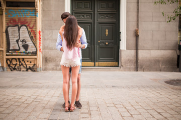 Back view of couple hugging in the street