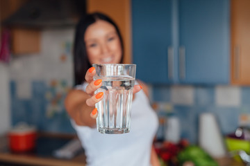 Woman is holding a glass of water and smiling.