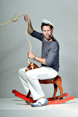 Sailor riding wooden horse with rope