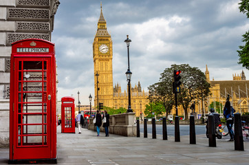 Big Ben on a Cloudy Spring Day with Traditional Red Phone Booths in Foreground Wall mural