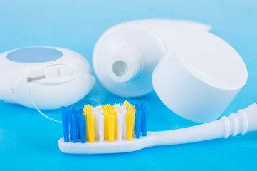 toothbrush, toothpaste and a thread on a blue background. Dental care for oral and dental hygiene