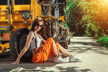 Sexy woman worker in overalls is sitting near the tractor.