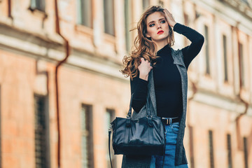 Beautiful glamour girl with handbag posing near old building .