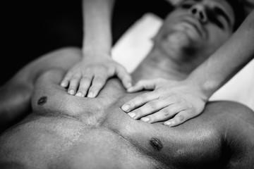 Sports massage. Massaging chest. Black and white