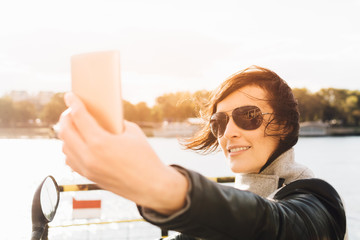 Young woman taking photo of herself on a motorbike