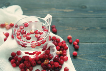 Fresh berries of a forest red cranberry in transparent glass with water among the scattered berries on a white linen cloth on a wooden surface of a table