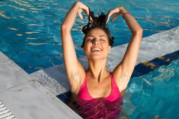 Young beautiful brunette woman enjoying swimming in the pool.
