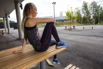 Sporty Young Woman Sitting On Wooden Bench At Park
