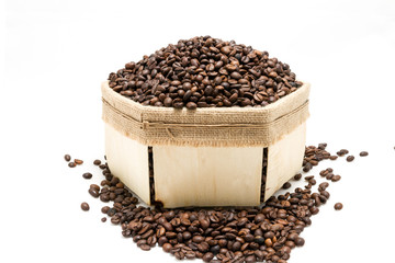 a lot of roasted coffee beans in a box made of natural materials on a white background